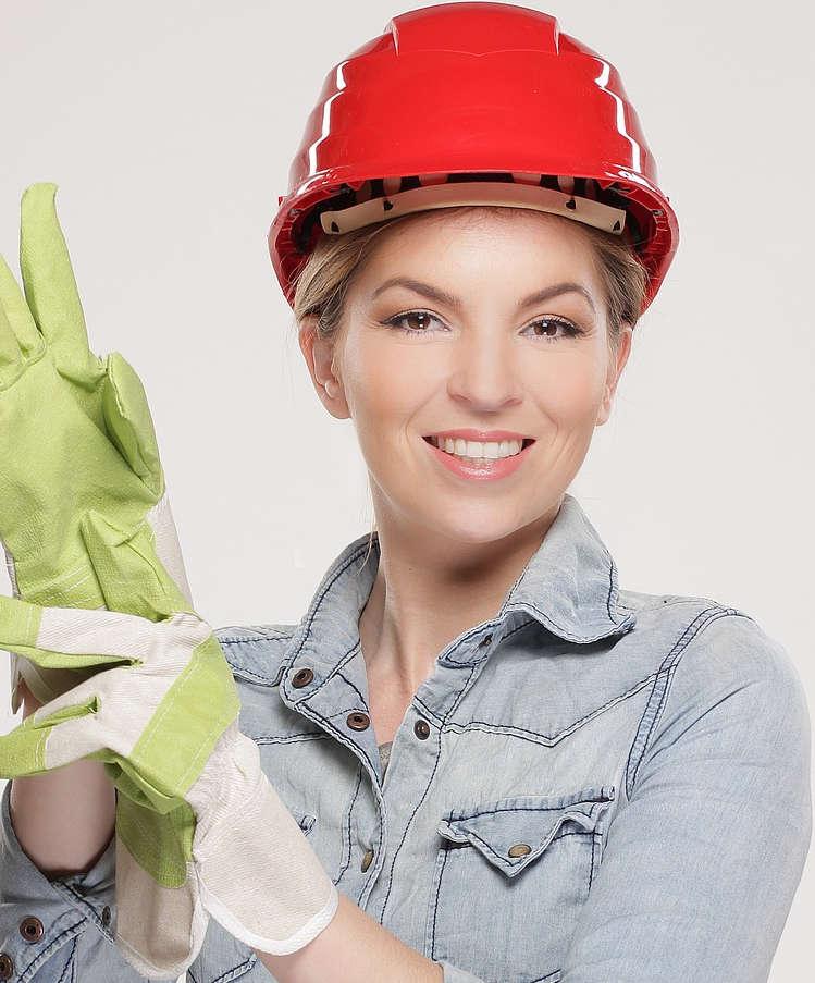 dolgozó nő, munkavédelmi sisakban integet